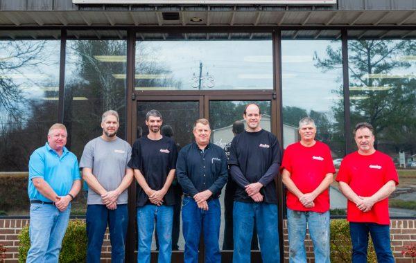 Photo showing the Automotive Collision Specialists team standing in front of the auto body collision and restoration repair shop.