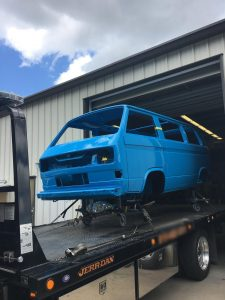 Photo of a freshly painted blue Volkswagen Vanagon leaving the Automotive Collision Specialists shop on a flatbed truck after paint and body restoration work.