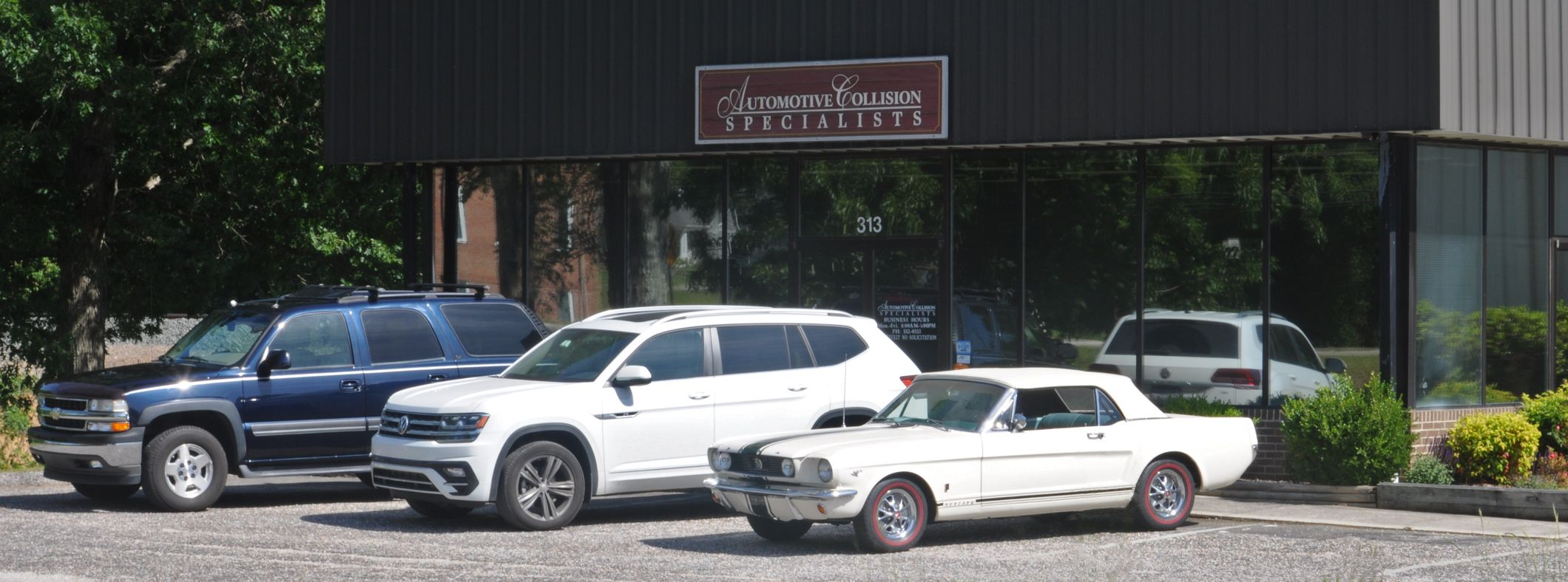 Photo of three cars that have been repaired or restored in front of Automotive Collision Specialists body shop.