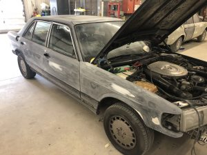 Front three quarter view of a Mercedes-Benz 560 SEL sedan in the Automotive Collision Specialists auto body repair shop being prepped for paint after a collision repair..
