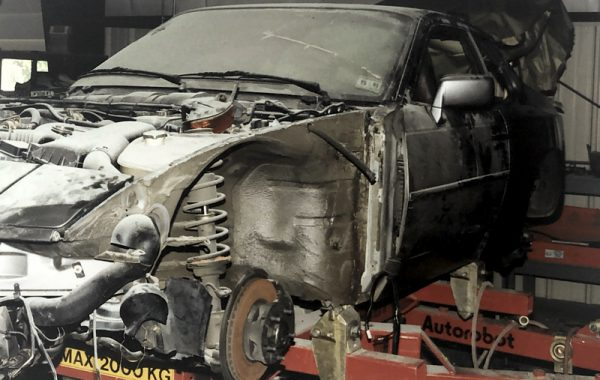 Photo of a black Porsche 944 on the frame rack at Automotive Collision Specialists during restoration in Fuquay Varina NC