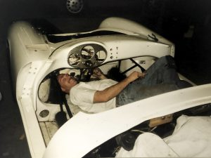 Photo of a white Porsche 550 Spyder with a technician working under the dashboard during a complete auto body restoration at the Automotive Collision Specialists shop in Fuquay Varina NC.