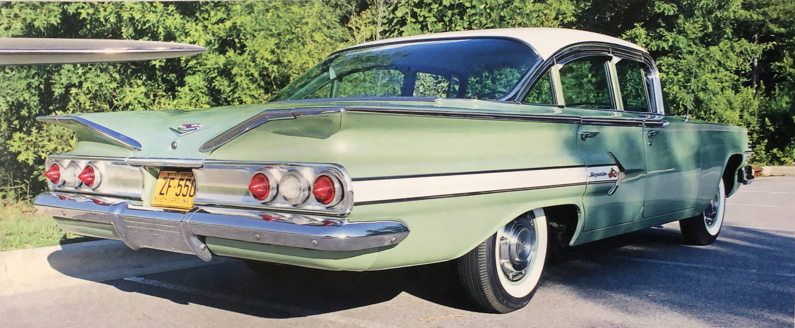Rear three quarter view of a green and white 1960 Chevy Impala from the October 2020 Generator & Distributor Magazine article featuring paint restoration by Automotive Collision Specialists in Fuquay Varina NC.