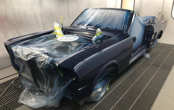 Photo of a dark blue 1966 Ford Mustang convertible in the paint booth at Automotive Collision Specialists in Fuquay Varina NC during a full restoration.