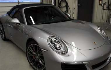 A front view of a late model silver Porsche Carrera convertible after bumper and body collision repair and windshield replacement by the Automotive Collision Specialists Repair Shop in Fuquay Varina NC.