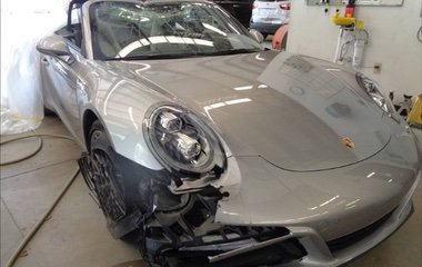 A front view of a late model silver Porsche Carrera convertible with bumper and body collision repair and windshield replacement by the Automotive Collision Specialists Repair Shop in Fuquay Varina NC.