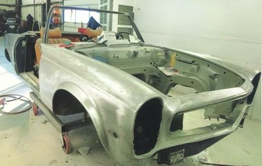 Front three quarter view of a 1970 Mercedes Benz 280 SL stripped of paint at Automotive Collision Specialists in Fuquay Varina NC during a concourse level restoration.