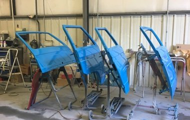 Photo of door panels on paint racks for a blue Volkswagen Vanagon after auto body repair and custom paint by Automotive Collision Specialists in Fuquay Varina NC.