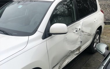 A side view of a white Toyota RAV4 SUV with side door damage before collision repair by the Automotive Collision Specialists Repair Shop in Fuquay Varina NC.