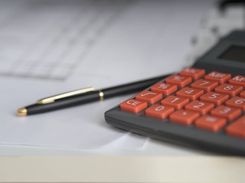 Photo of a calculator and paperwork to show who pays the deductible after a car accident repair.
