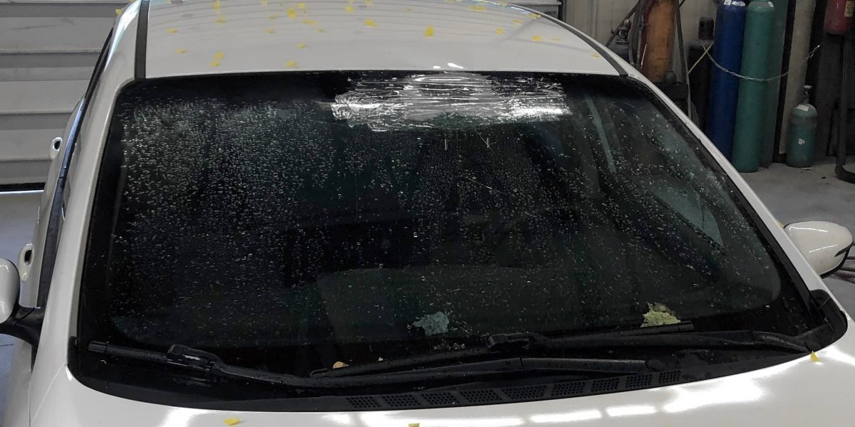 Photo of a white hatchback covered with yellow stickers showing hail impact points. At the Automotive Collision Specialists auto body and paint repair shop near Fuquay Varina NC for automotive hail damage repair.